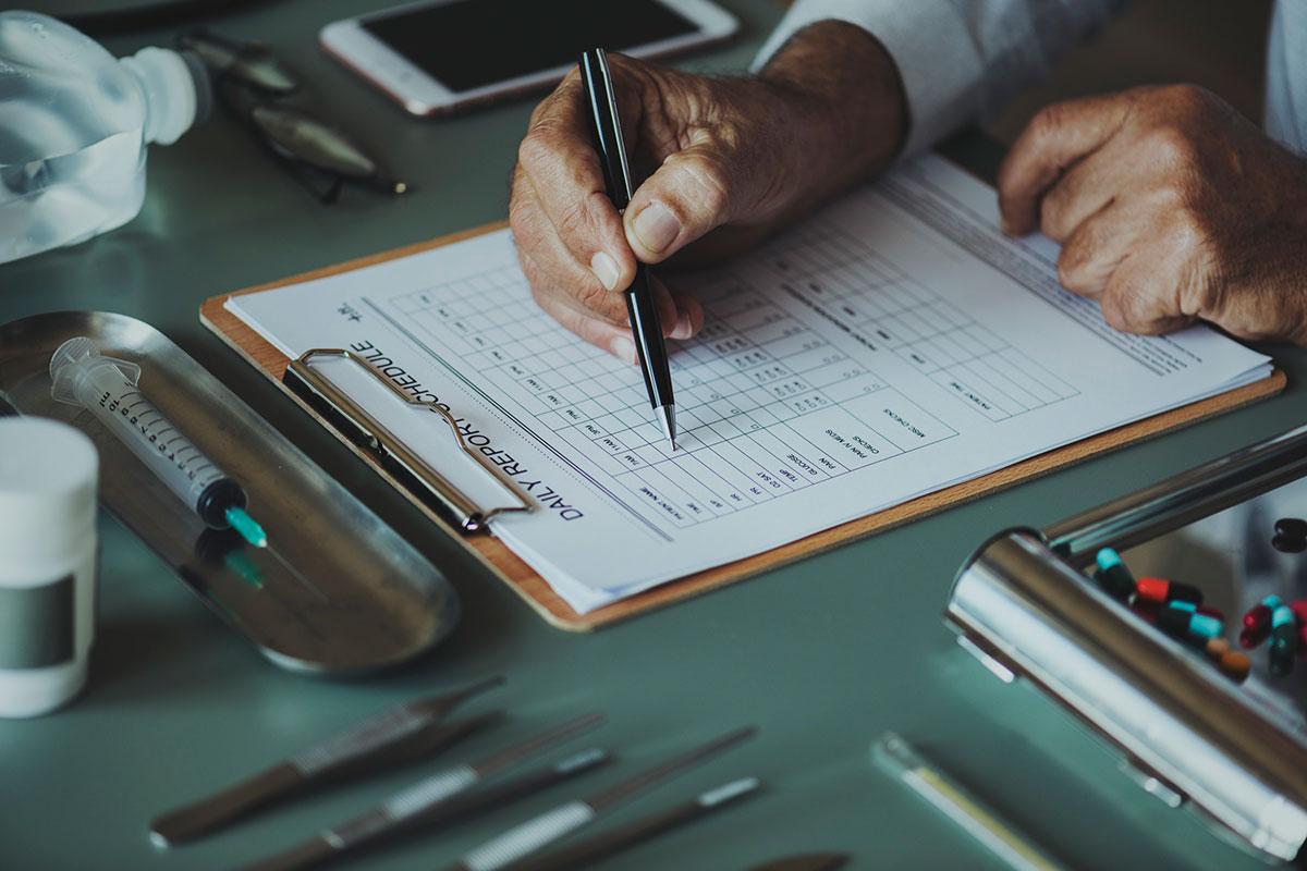 foto di dottore che scrive su cartella clinica